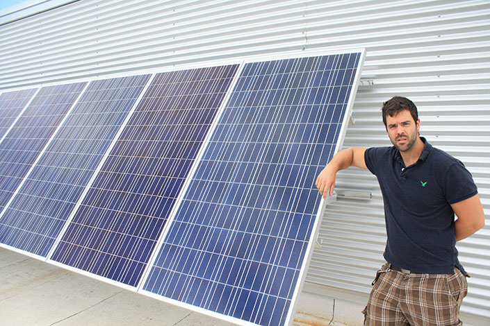 Jon Chiasson standing next to a row of solar panels on a roof.