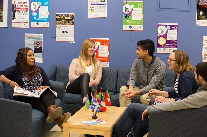 Cinq étudiants discutent ensemble, assis autour d'une table à café sur laquelle sont déposés des drapeaux de pays de langue française