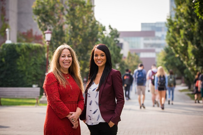 Two smiling women stand next to each other on the university campus.