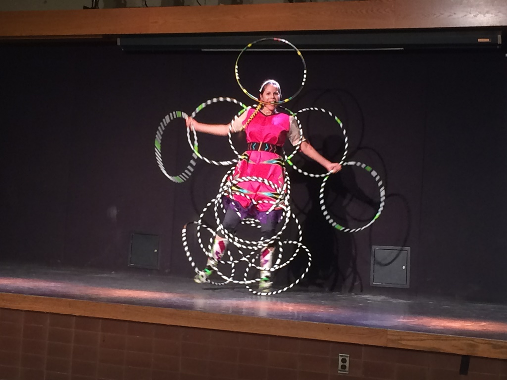 A woman is doing an Algonquin hoop dance, which involves dancing while intertwining many hoops in intricate patterns along her arms, around and across her torso and around both legs. She is also holding a hoop in her mouth.