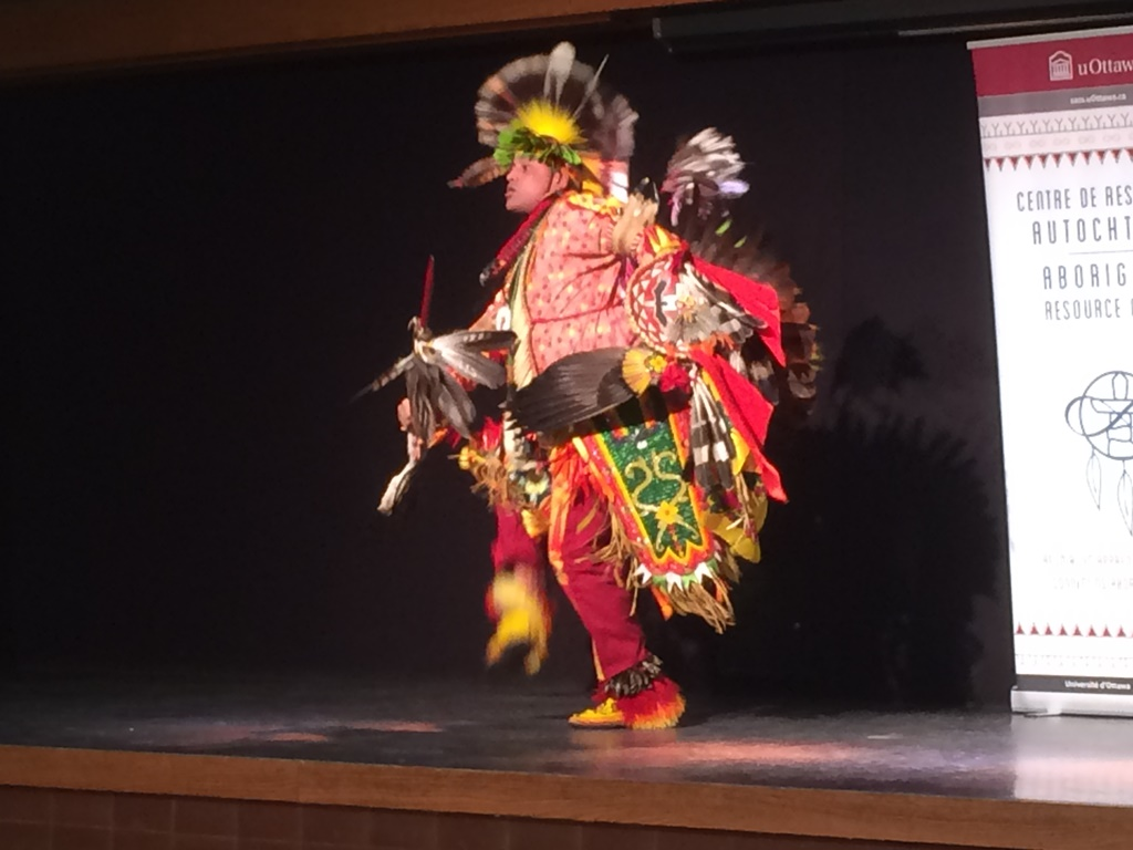A man in an Indigenous costume and feathered headdress is dancing on stage.