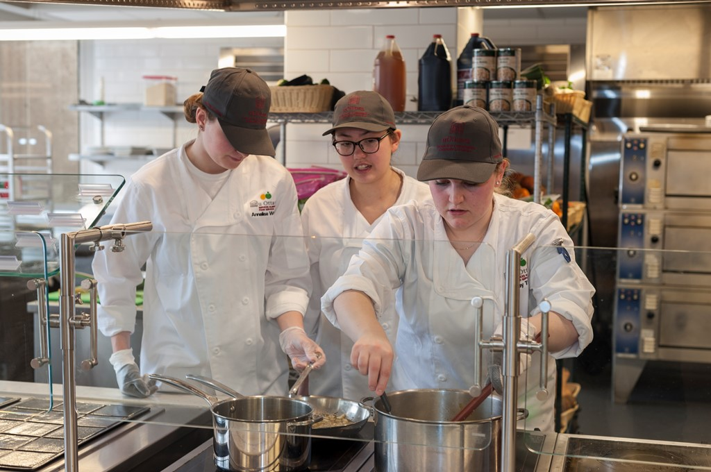 Three women wearing caps stirring pots on a stove.