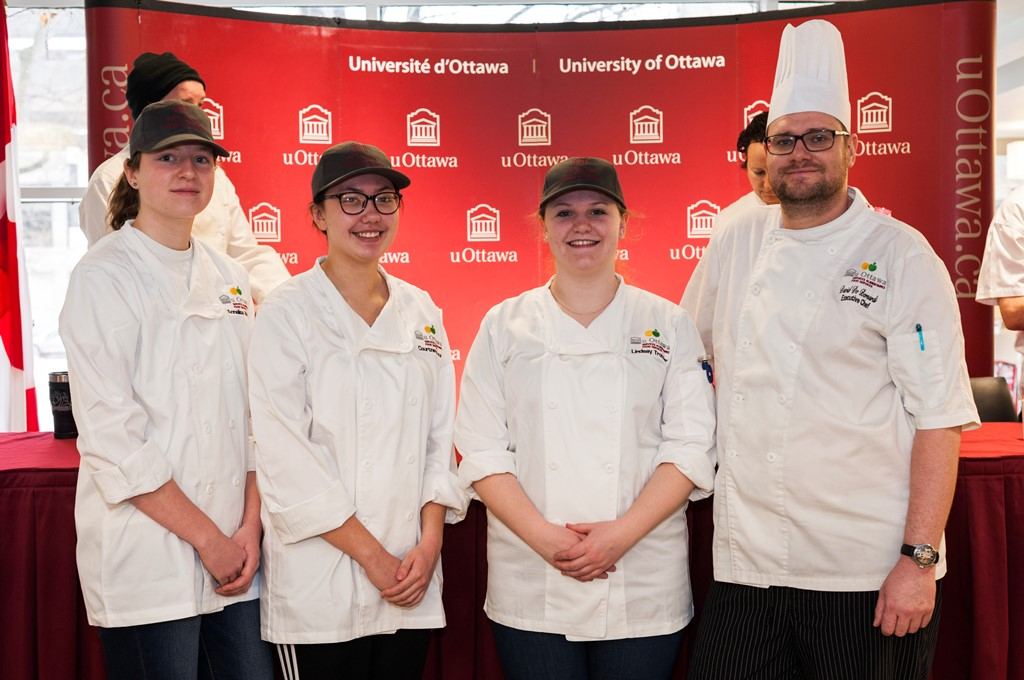 Three women in white aprons next to a man in a chef's hat with a poster showing uOttawa's logo in the background.