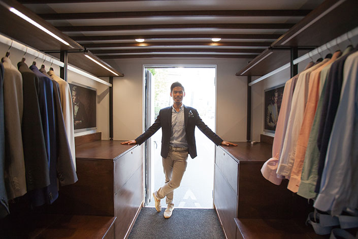 Nathon Kong stands inside his tailoring truck, wearing brown pants and a blazer.