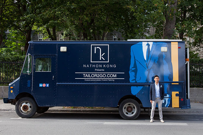 Nathon Kong Stands outside his truck smiling with a hand in his pocket.