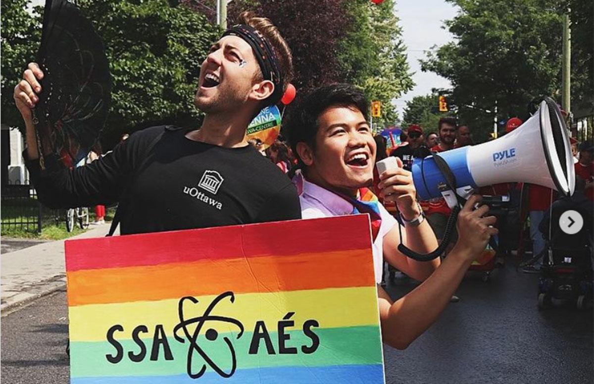Jesse Lesniowski et Dasa Soekotjo tenant un panneau avec l'arc-en-ciel de la fierté gaie et le logo de l'Association des étudiants en sciences