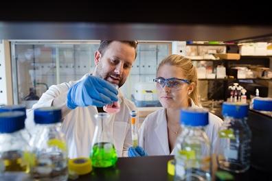 Alexandre Poulain et Jessica Gaudet observent des béchers et des éprouvettes dans un laboratoire.