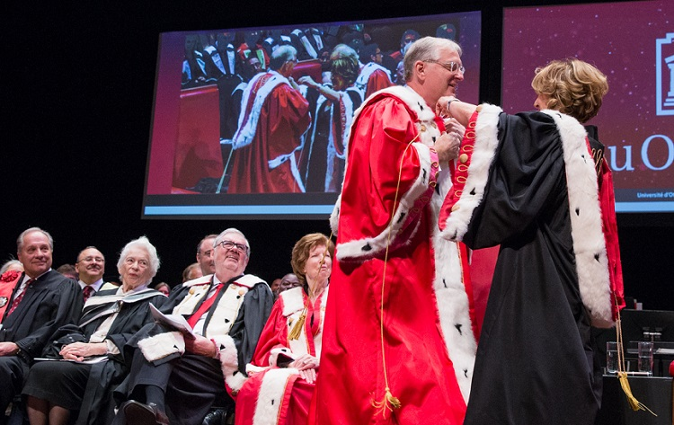 University dignitaries sit on stage wearing ceremonial robes as University president Jacques Fremont has his robe adjusted by Mona Nemer, vice-president, research.