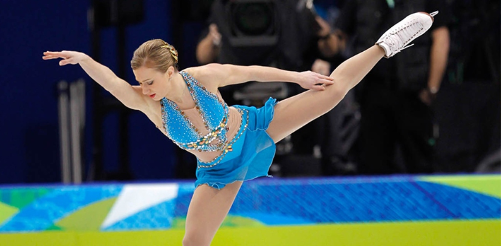 Olympic figure skater Joannie Rochette with her arm extended and leg raised during a performance