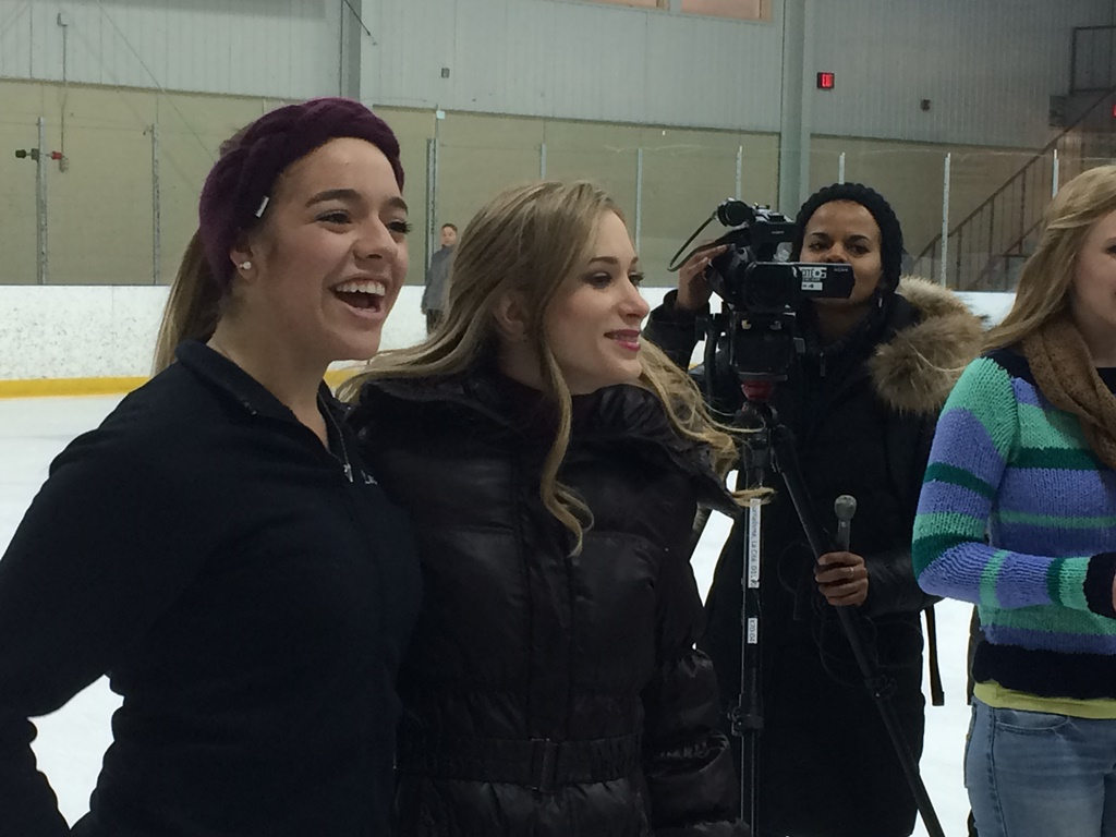 Laura Hernandez and Joannie Rochette smiling on arena ice, surrounded by other people.
