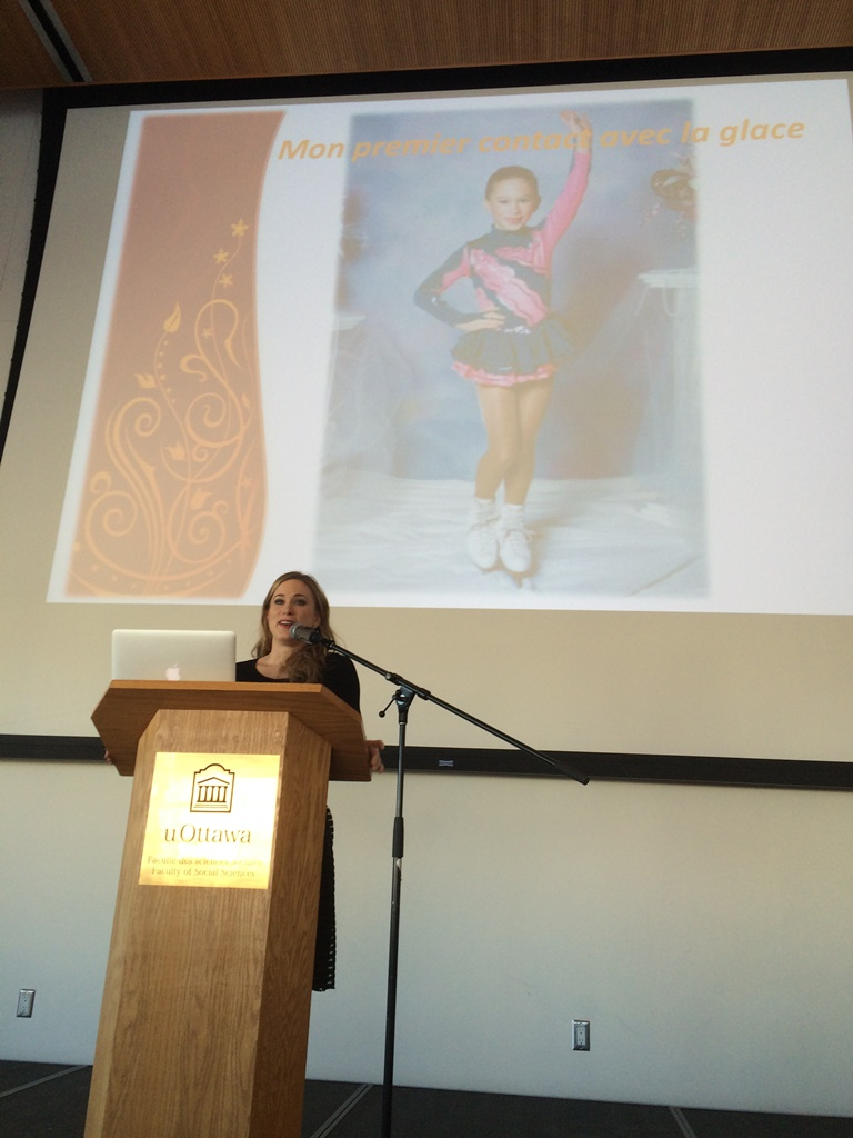 Joannie Rochette at a podium with a screen behind showing a photo of her as a young girl in a figure skating pose.
