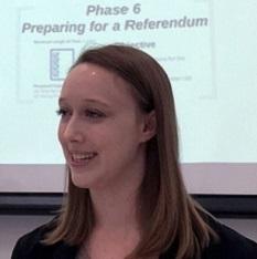 Une jeune femme souriante se tient debout sur un podium. Sur un écran derrière elle, une diapositive projette en anglais les mots « Phase 6 – Se préparer à un référendum ».
