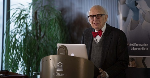 Eric Kandel stands at a lectern giving a presentation at the University of Ottawa.