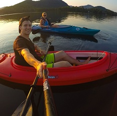 A young man and young woman sit in kayaks on a lake at sunset. The man extends his arm, holding the Spivo Stick.