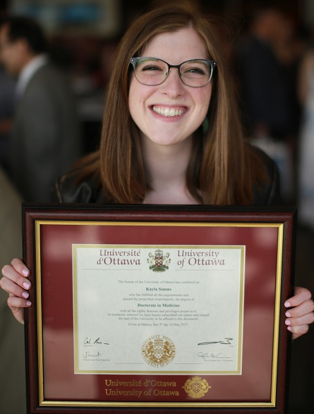 Kayla Simms holding her MD degree