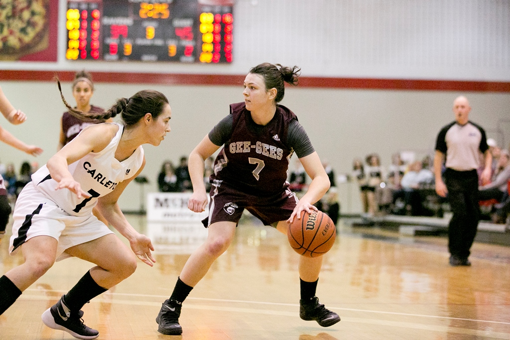 Kellie Forand dribbling a basketball as opposing woman player in Carleton shirt approaches.