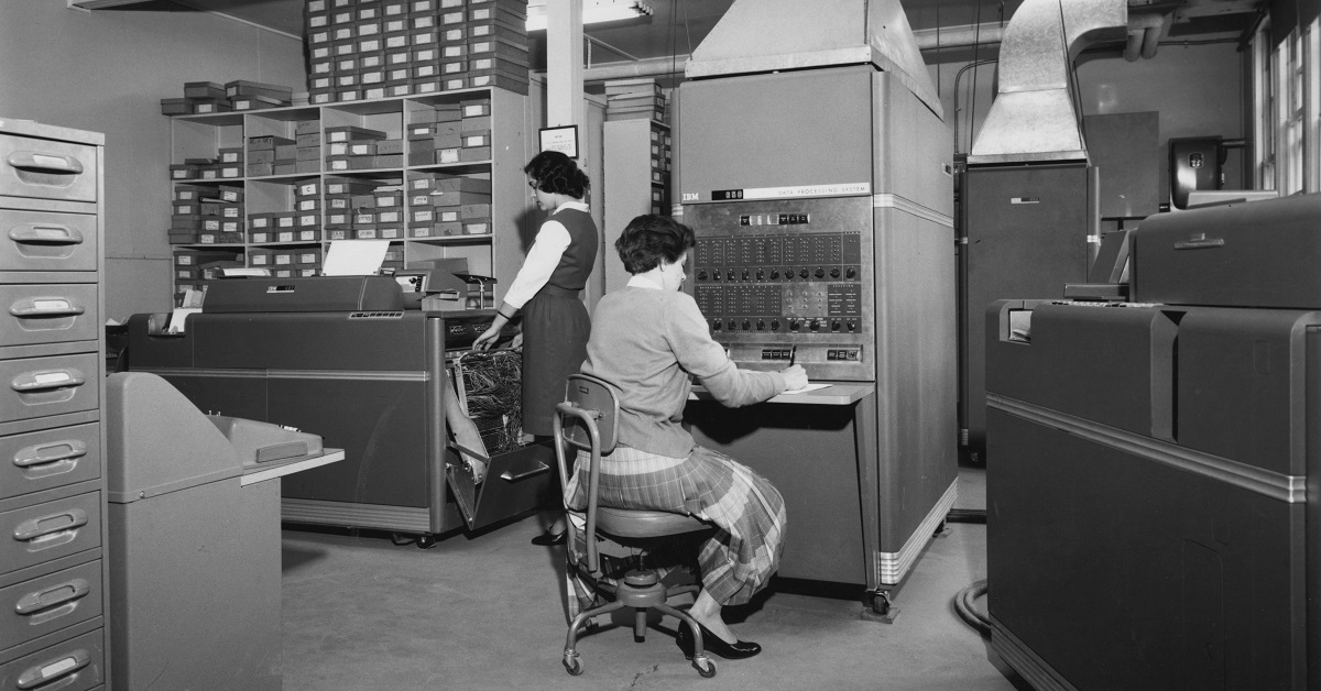 A woman sits at an early computer and another woman stands nearby.