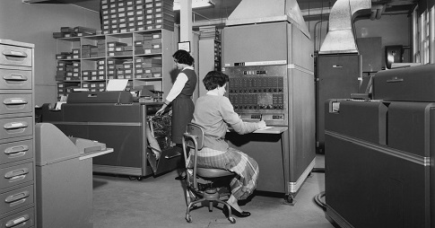 Une femme est assise à un ordinateur de première génération alors qu'une autre se tient à ses côtés.