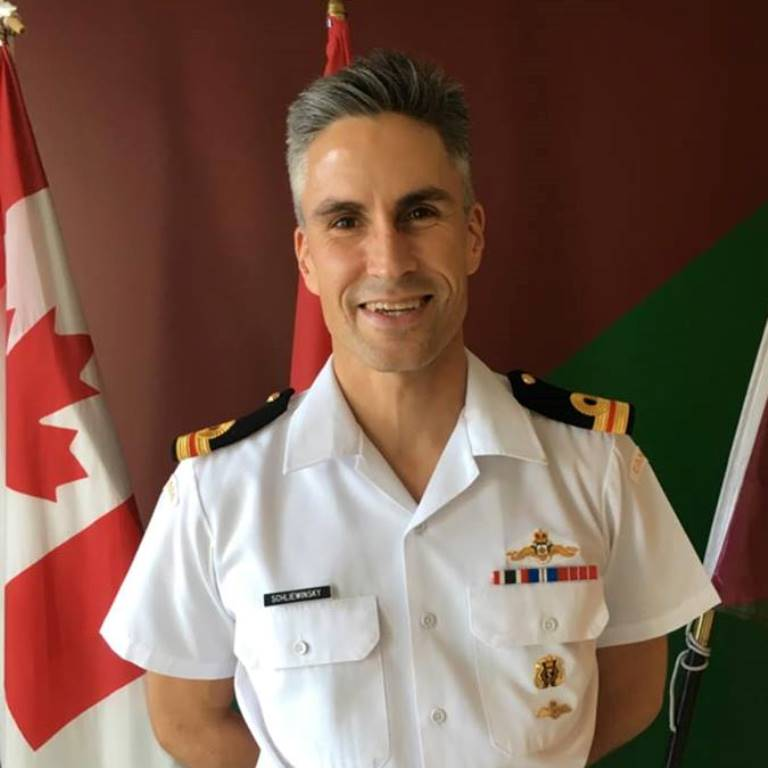 A smiling Kharim Schliewinsky in his crisp military uniform standing in front of a Canadian flag