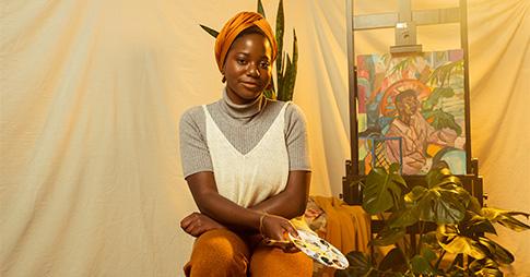 Portrait de Laurena Finéus assise à côté d'une de ses œuvres d'art
