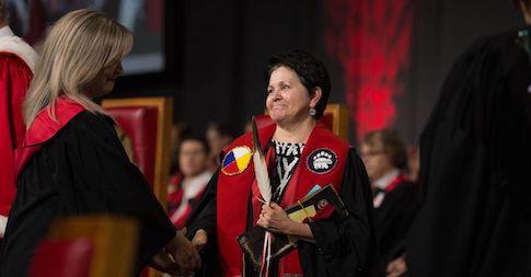 Étudiante vêtue d'une toge de graduation reçoit un diplôme à la collation des grades.