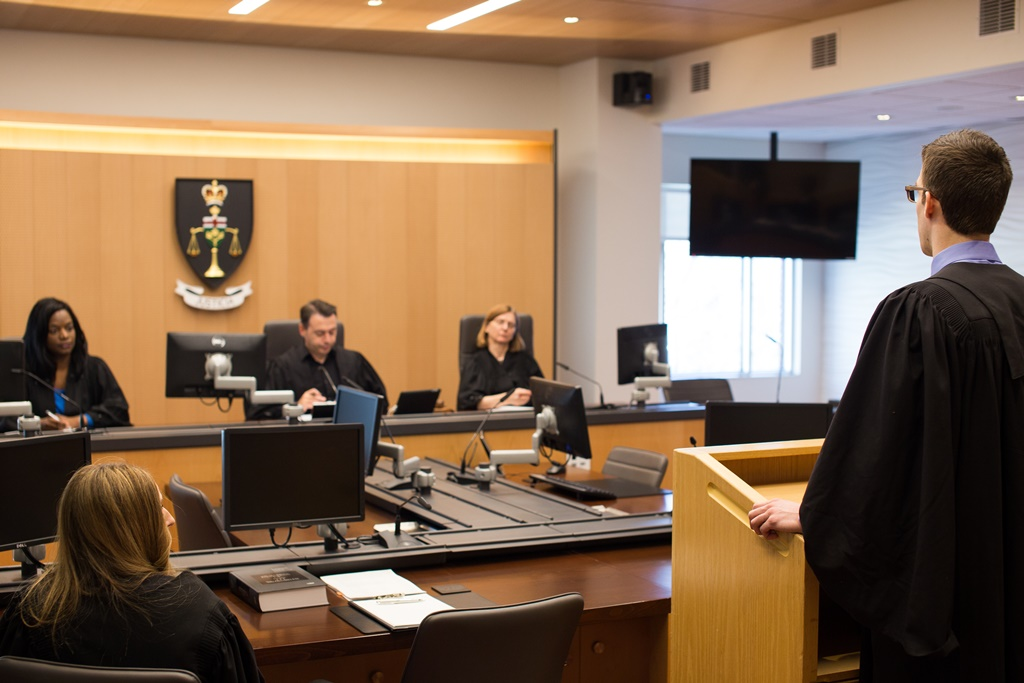 Image of a courtroom with three judges presiding on a panel and the back of a lawyer wearing a black gown in the foreground.