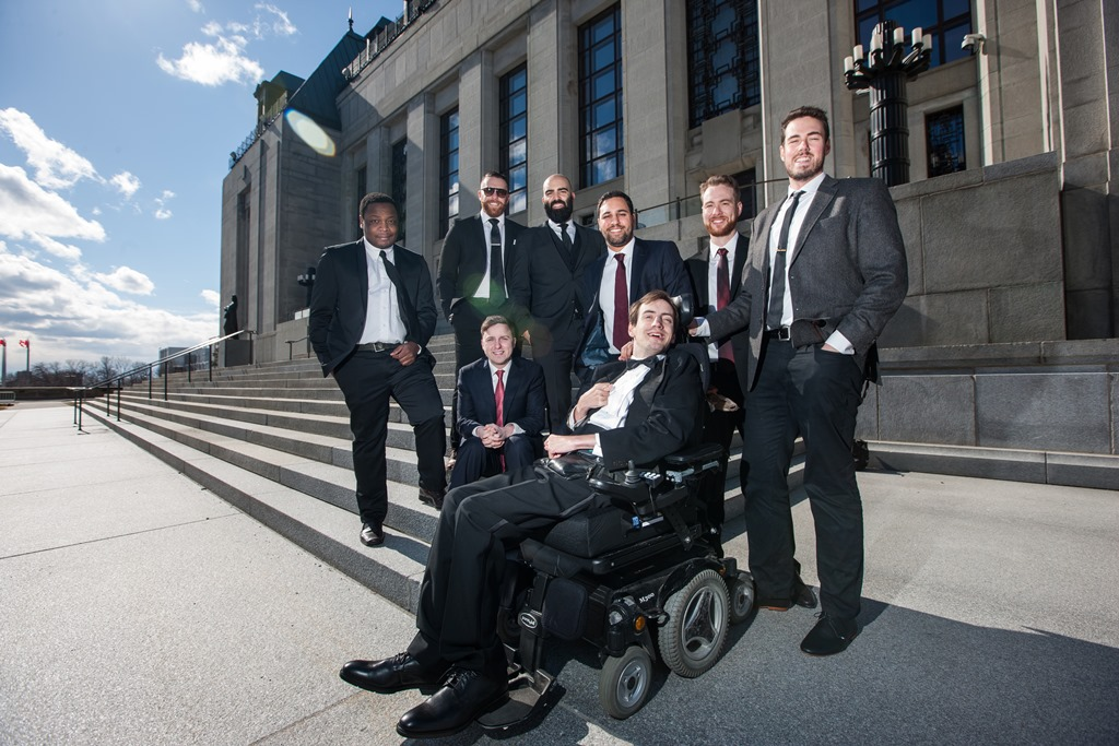 Group of seven men with another man in a motorized wheelchair in front of the steps of the Supreme Court of Canada
