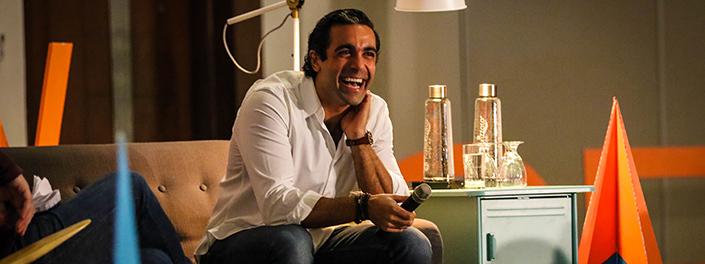 Assis sur un sofa, Omar Itani rit en tenant un micro.