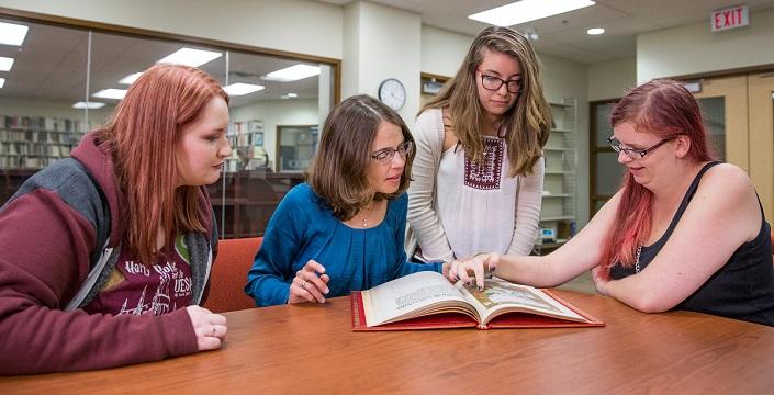 Quatre femmes regardent un livre ouvert sur une table.