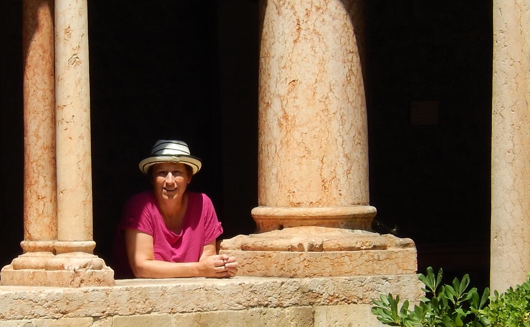 Femme debout entre des colonnes.