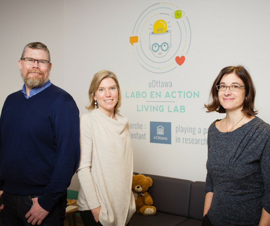 Professors in front of a wall with the Living Lab logo.