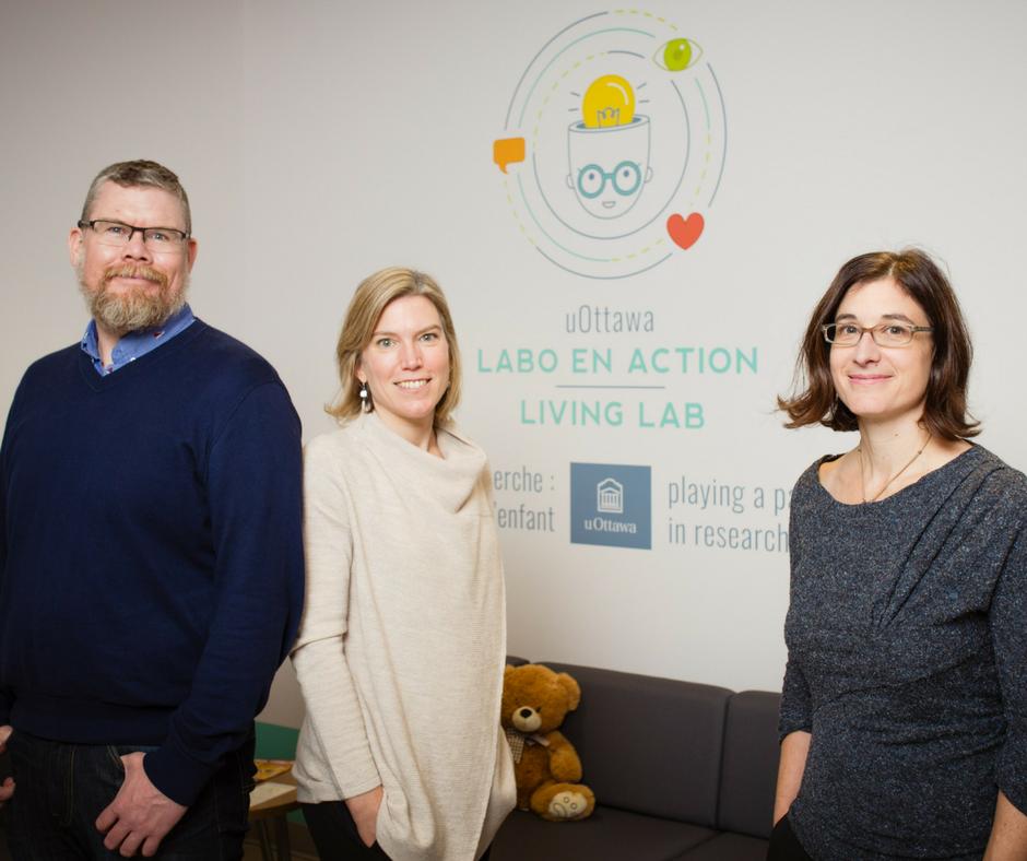 Chris Fennell, Cristina Atance et Tania Zamuner debouts dans la salle d'accueil du Labo en action.