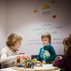 Cristina Atance and two young children playing with toys on a table.