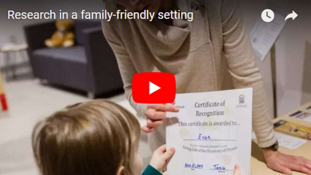 A woman is handing a certificate to a child. The Youtube logo is at the centre of the image.