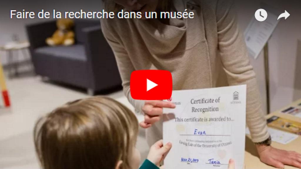 Une femme remet un certificat à un enfant. Le logo de Youtube est au centre de l'image.