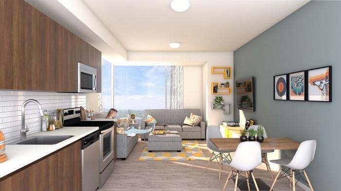 Une cuisine et un salon à aire ouverte. On y retrouve des électroménagers modernes et de larges fenêtres.