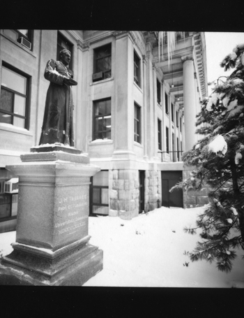 Black and white photo of the Tabaret statue next to Tabaret hall.