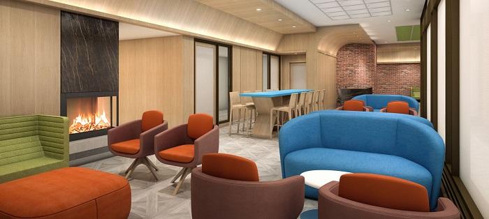Un salon avec un foyer, et un grand nombre de fauteuils et de causeuses.