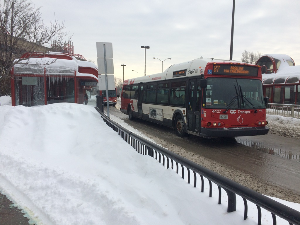 A bus approaches a stop on the Transitway