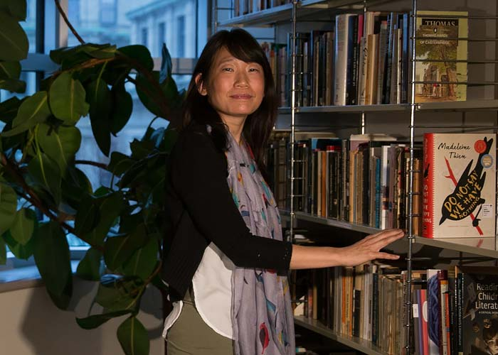Madeleine Thien stands beside shelves full of books, including her novel, Do Not Say We Have Nothing.