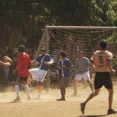 Des jeunes jouent au soccer sur un terrain sablonneux.