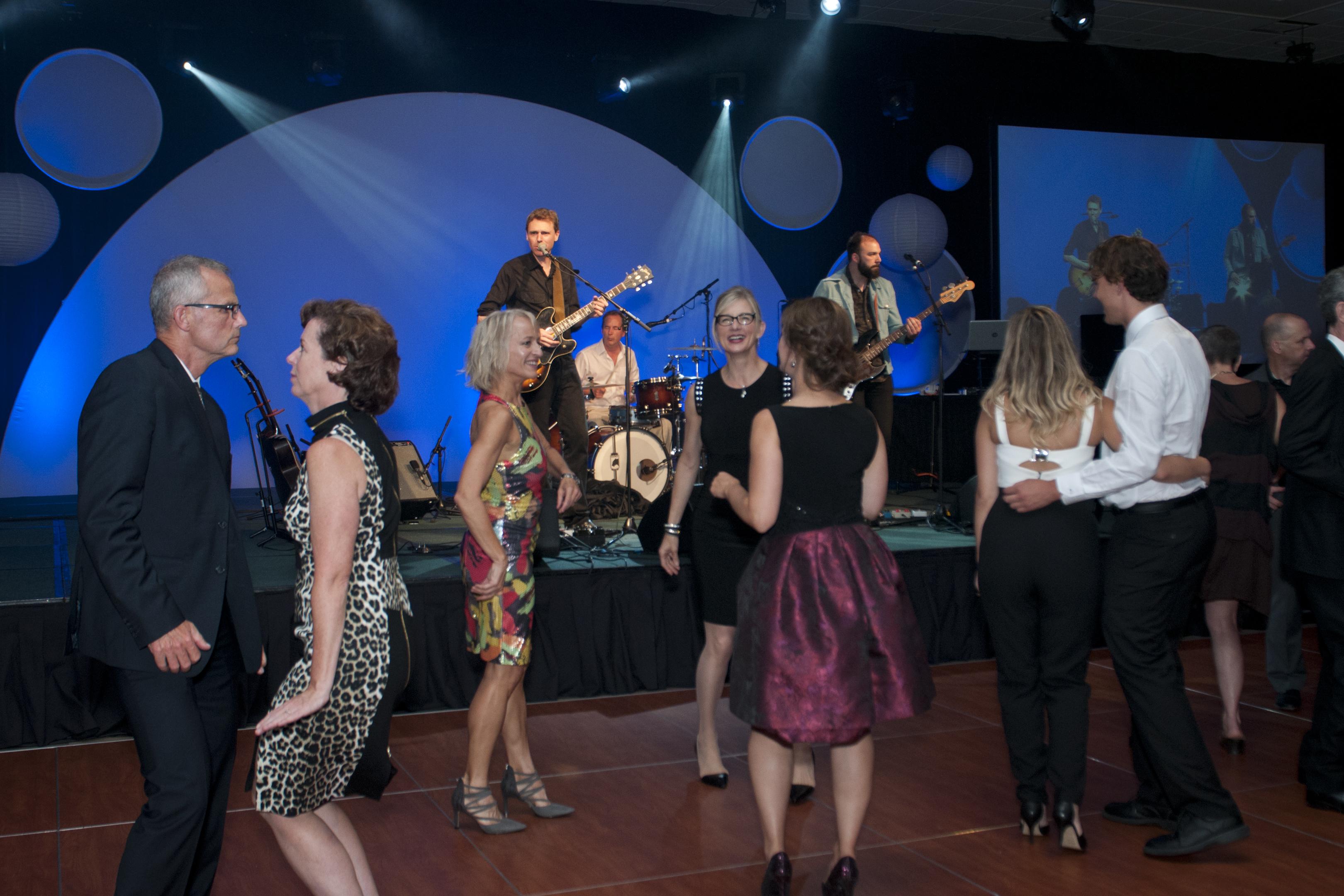 Des hommes et des femmes en tenue de soirée dansent au son de la musique d'un orchestre.
