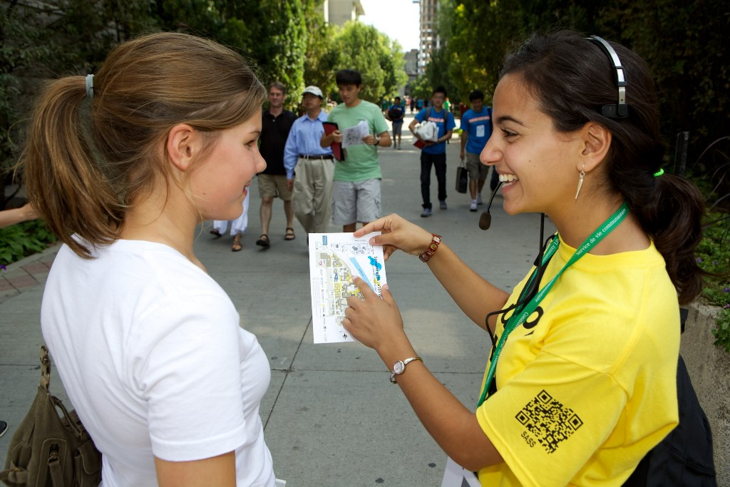 A female student gives directions to another female student