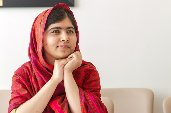 Malala wearing a patterned headscarf sits with both hands resting under her chin.