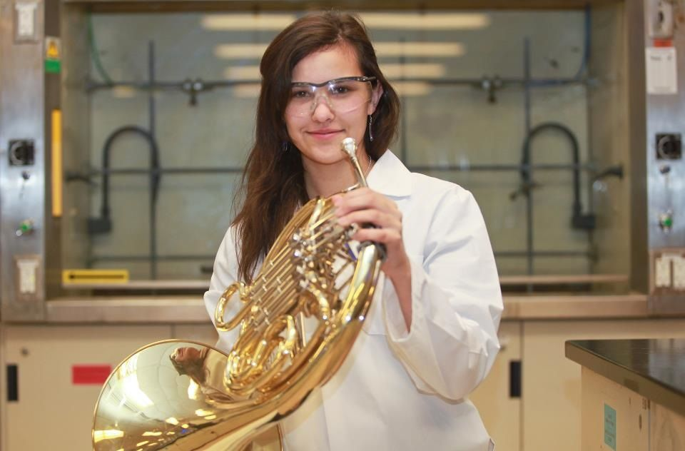 Margaret Watson is holding a french horn, safety glasses on her face.