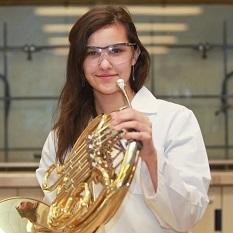 Une jeune femme tient un cor français, des lunettes de sécurité sur son visage.