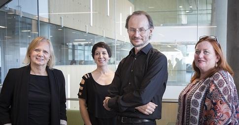 Trois femmes et un homme, debout côte à côte.