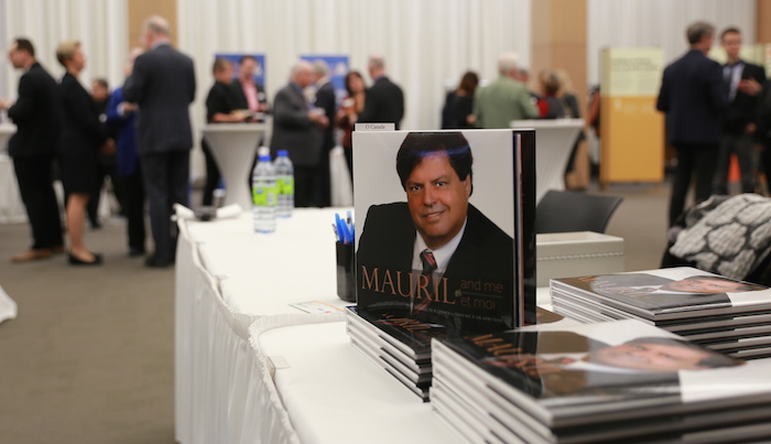 On a table, copies of a book with a cover photo of Mauril Bélanger; event attendees chat in the background.