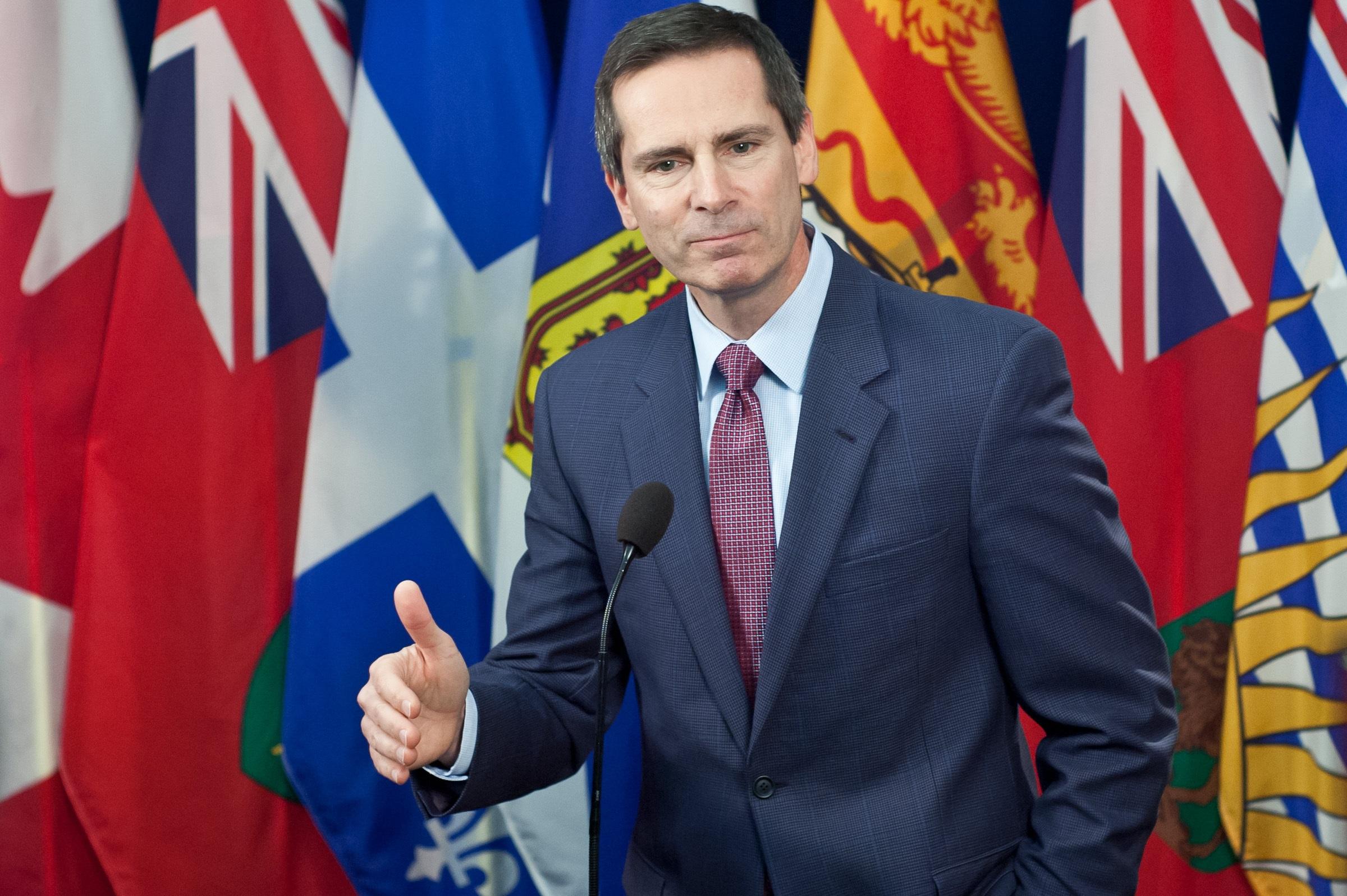 Dalton McGuinty debout devant les drapeaux des provinces canadiennes.