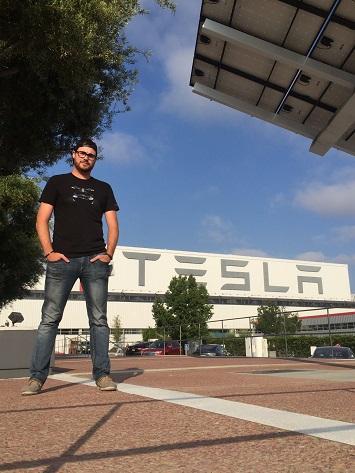 Un jeune homme, les mains dans les poches, debout devant un édifice arborant le logo de Tesla.